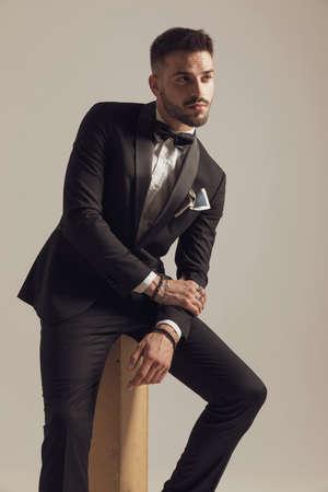 Hopeful groom leaning on leg and looking away, wearing tuxedo while sitting on gray studio background Imagens