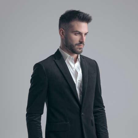 Serious elegant man looking away and wearing suit while walking on gray studio background