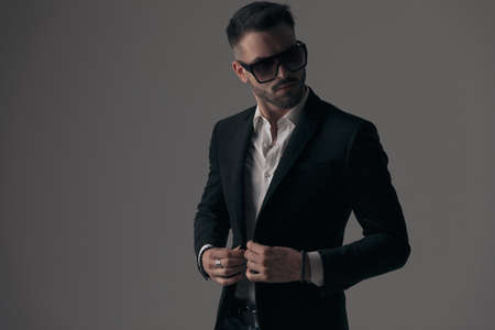 Mysterious fashion model closing his jacket, wearing suit and sunglasses while standing on gray studio background