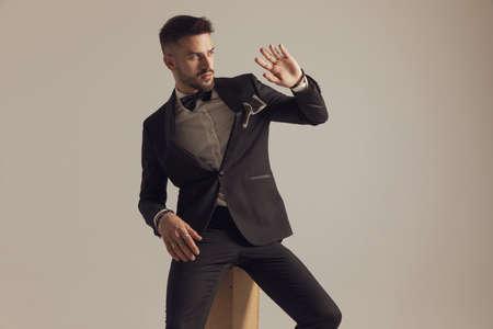 Confident groom holding his hand as blocking something, wearing tuxedo while sitting on gray studio background