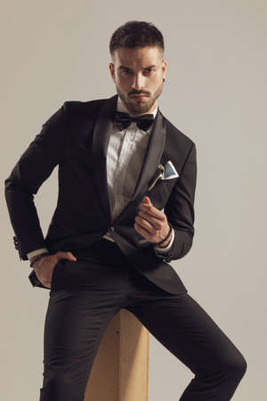 Serious groom holding hand in pocket and gesturing money, wearing tuxedo while sitting on gray studio background Imagens