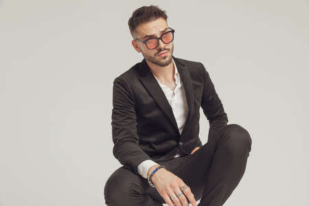 Eager fashion model looking away and wearing sunglasses while crouching on gray studio background