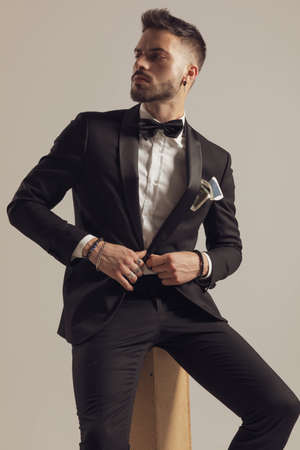 Confident groom unbuttoning his jacket and looking away, wearing tuxedo while sitting on gray studio background
