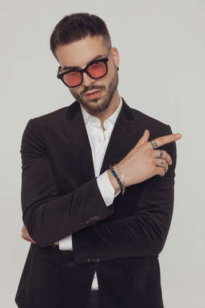 Charming fashion model pointing away and wearing sunglasses while standing on gray studio background Imagens