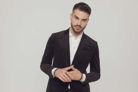 Attractive fashion model wearing suit and holding hands together, standing on gray studio background