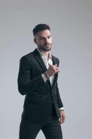 Confident elegant man wearing suit while walking on gray studio background
