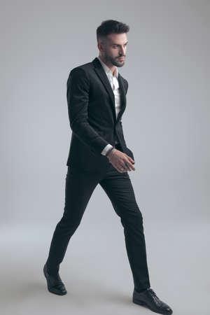 Charming elegant man wearing suit and walking on gray studio background