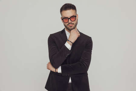 Tough fashion model holding his fist clenched, wearing sunglasses while standing on gray studio background