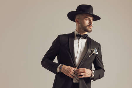 Pensive groom fixing his jacket and looking away, wearing hat and tuxedo while standing on gray studio background Imagens