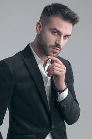 Charming elegant man holding hand on chin and thinking, wearing suit while standing on gray studio background Imagens