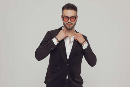 Serious fashion model fixing collar and wearing sunglasses while standing on gray studio background