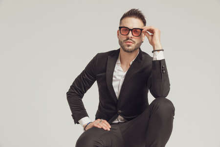 Charming fashion model adjusting his sunglasses while crouching on gray studio background