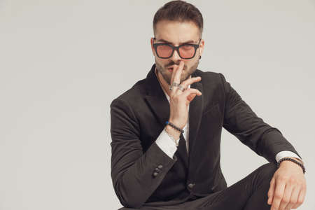 Attractive fashion model gesturing silence, wearing sunglasses while crouching on gray studio background