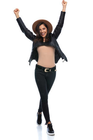 Cheerful casual woman celebrating, wearing hat and leather jacket while stepping on white studio background