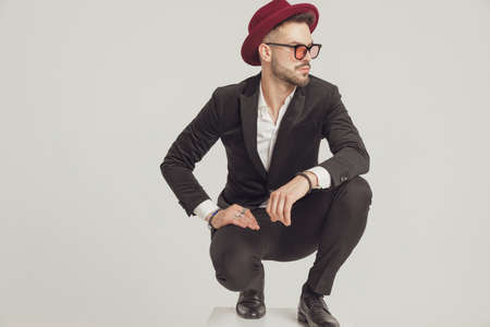 Pensive fashion model looking away, wearing sunglasses and hat while crouching on gray studio background Imagens