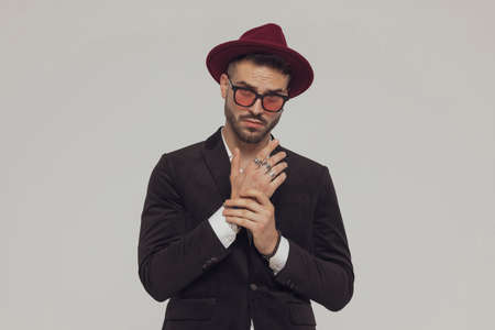 Charming fashion model arranging his sleeve, wearing hat and sunglasses while standing on gray studio background