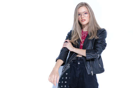 Tough fashion model adjusting her sleeve, wearing glasses and leather jacket while standing on white studio background