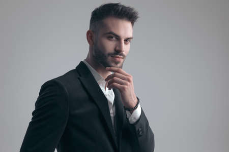 Pensive elegant man holding hand on chin, wearing suit while standing on gray studio background Imagens