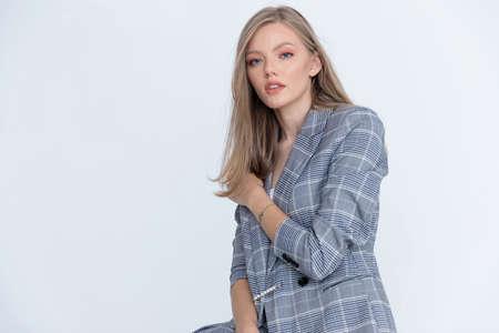 Charming businesswoman adjusting her jacket while sitting on white studio background