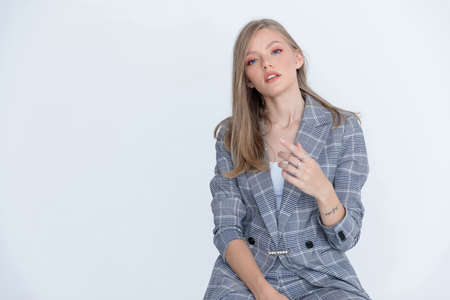 Charming businesswoman wearing suit and explaining while sitting on white studio background