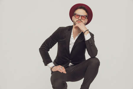 Suspicious fashion model holding hand on chin, wearing sunglasses and hat while crouching on gray studio background Imagens