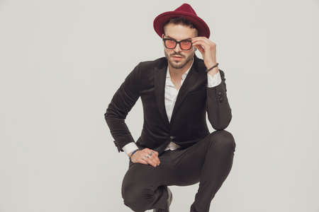 Tough fashion model fixing his sunglasses and looking away, wearing hat while crouching on gray studio background