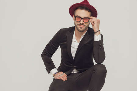 Positive fashion model taking off his sunglasses and smiling, wearing hat while crouching on gray studio background