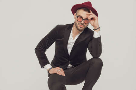 Tough fashion model fixing his hat and wearing sunglasses while crouching on gray studio background