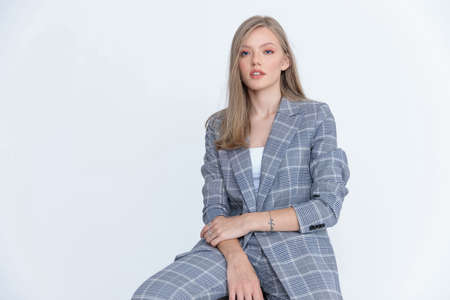 Serious businesswoman posing and wearing suit while sitting on white studio background