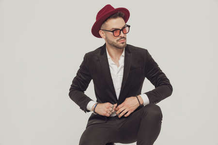 Confident fashion model adjusting his jacket, wearing sunglasses and hat while crouching on gray studio background Imagens
