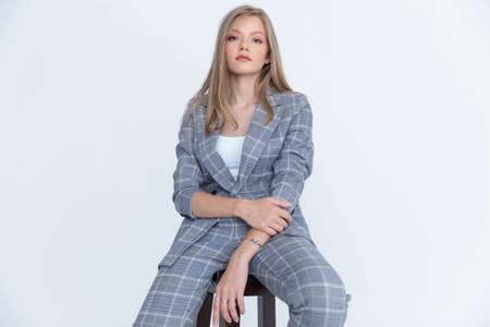 Serious businesswoman posing while sitting on white studio background