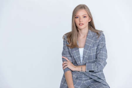 Positive businesswoman wearing suit and sitting on white studio background