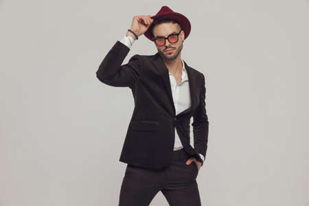 Confident fashion model adjusting his hat with hand in pocket, wearing sunglasses while standing on gray studio background