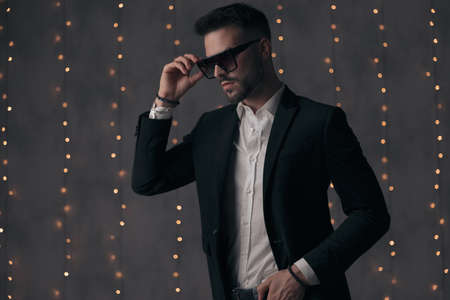 Confident fashion model taking off his sunglasses and looking away while standing on gray studio background with lights Imagens