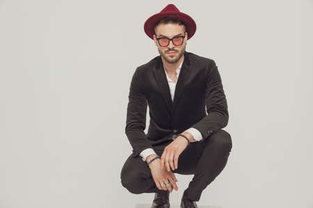Confident fashion model looking forward, wearing hat and sunglasses while crouching on gray studio background