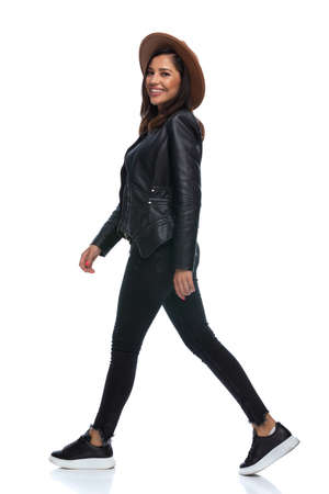 Side view of happy casual woman laughing, wearing hat and leather jacket while walking on white studio background Imagens