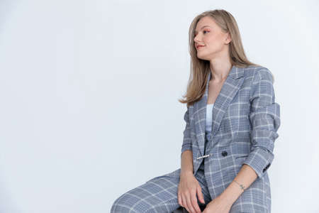 Friendly businesswoman looking away and smiling while sitting on white studio background Imagens