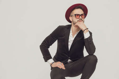 Thoughtful fashion model holding hand on chin, wearing sunglasses and hat while crouching on gray studio background