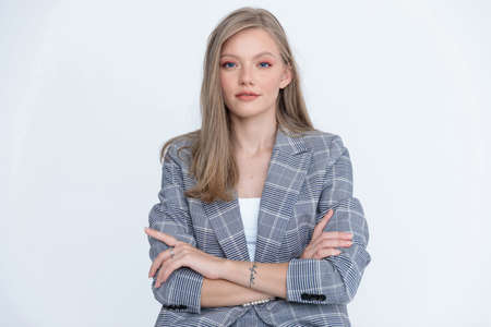 Confident businesswoman holding her arms crossed and wearing suit while sitting on white studio background
