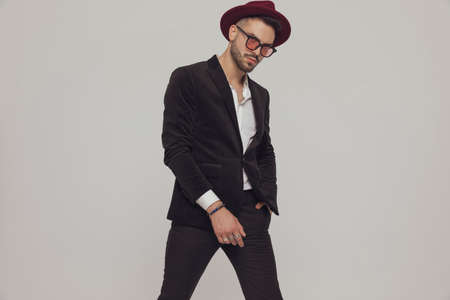 Serious fashion model holding hand in pocket, wearing hat and sunglasses while standing on gray studio background