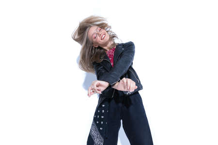 Cheerful fashion model holding hand crossed and dancing, wearing glasses and leather jacket on white studio background