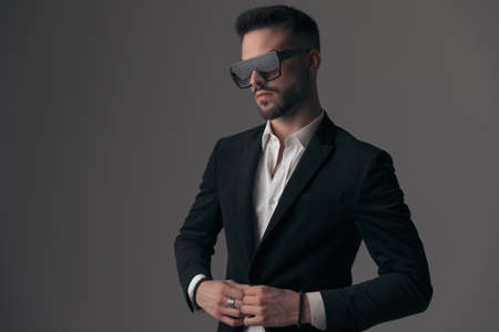 Confident fashion model fixing his jacket and looking away, wearing suit and sunglasses while standing on gray studio background