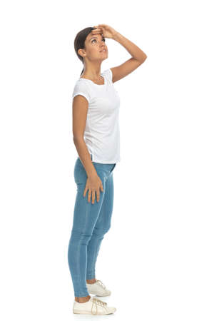 Side view of hopeful casual woman looking into distance, standing on white studio background