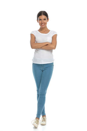 Positive casual woman smiling with hands and legs crossed, standing on white studio background