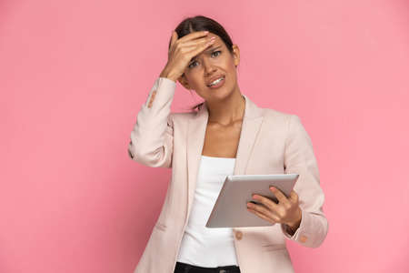 beautiful businesswoman holding her tablet and slapping her face, feeling anxious on pink background Banque d'images