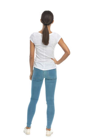 Back view of casual woman holding hand oh hip while standing on white studio background