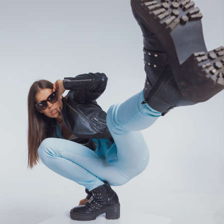 Tough fashion model holding sunglasses and kicking with her leg, crouching on gray studio background Banco de Imagens