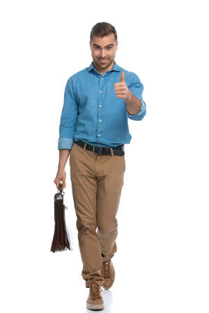 happy casual man walking towards the camera while giving a thumbs up and holding a briefcase against white background