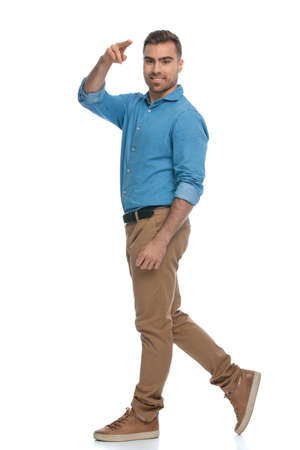 attractive casual man walking on his way and saluting someone against white background