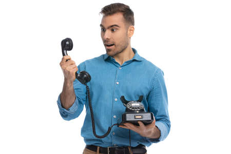 casual man being surprised by the news he heard on the telephone against white background